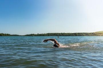 Man swimming in a lake, open water swim in summer