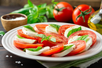 Italian caprese salad with tomatoes, mozzarella cheese and basil in plate on dark wooden background