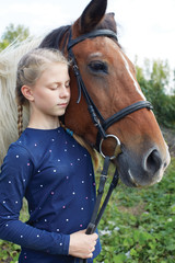 Portrait of young horsewoman and brown horse. Girl with horse.
