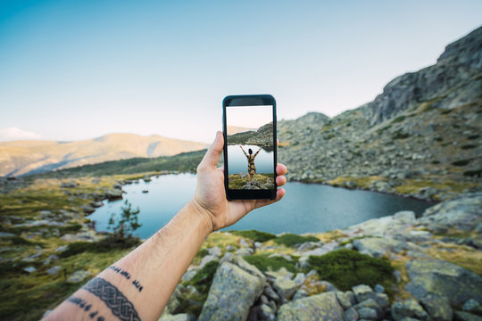 Crop man holding phone with picture innature