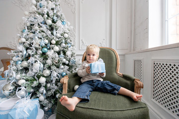 Blond little boy unpacks a gift. Happy new year. decorated Christmas tree. Christmas morning in bright living room. sitting on green chair
