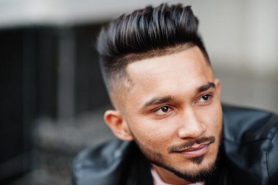 Stylish indian beard man at black leather jacket. India model posed sitting at streets of city. Close up portrait.