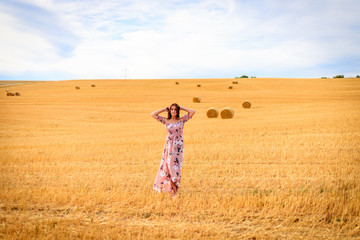 Young woman in summer dress in a stubble field waving with arms