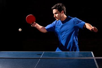 Deportista jugando tenis de mesa sobre fondo negro.