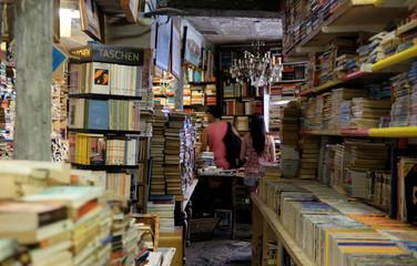 """Consumers look at books inside the """"Acqua Alta"""" bookstore in Venice"""