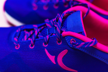 Ultra blue violet pink female sneakers on pastel pink background flat lay top view with copy space selective focus. Sports shoes, fitness, concept of healthy lifestile, everyday training.