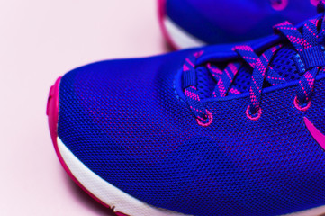 Ultra blue violet pink female sneakers on pastel pink background flat lay top view with copy space. Sports shoes, fitness, concept of healthy lifestile, everyday training.