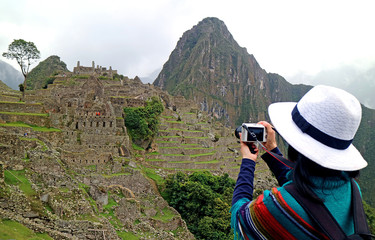 One female tourist taking picture of the Inca ruins in Machu Picchu, the famous archaeological site in Cusco region of Peru