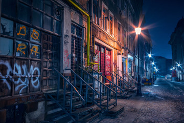 Beautiful old alley with old buildings shot in the night well illuminated by street lamps Fototapete