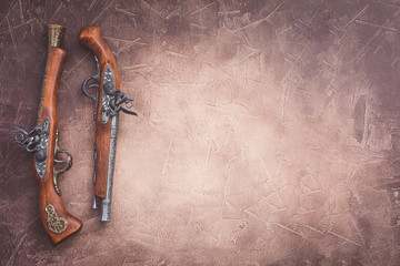 Two vintage duel pistols on wooden background