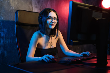 Portrait of the beautiful professional gamer girl playing in online video game, casual cute geek wearing glasses, talks and chats with her teammates and friends through headphones. neon colored