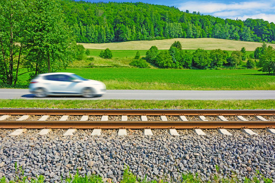 A fast moving car along the road goes alongside the railway tracks. Tracks running next to the road. A sunny view of a car passing through the countryside