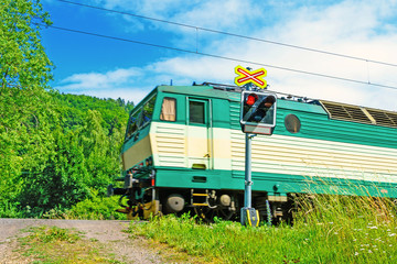 Semaphores in front of the railway crossing. A train crossing a railway crossing. Warning signaling on railway in the Czech Republic.