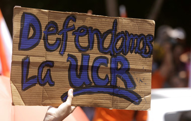 """An university student holds a sign reading """"We defend the University of Costa Rica"""" during a march against a tax reform proposed by the government in San Jose"""