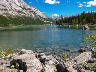 The clear water of Medicine Lake surrounded by mountains on a sunny day, Jasper National Park, Alberta, Canada