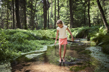 Child cute blond girl playing in the creek. Girl walking in forest stream and exploring nature. Summer children fun. Children summer adventure
