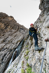young attractive female mountain climber on a difficult Via Ferrata in the Dolomites in Alta Badia in the South Tyrol in Italy