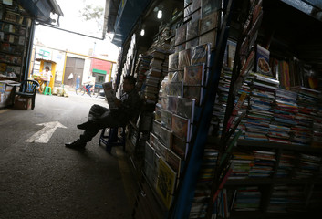 A man reads a newspaper at a second-hand book market in Lima