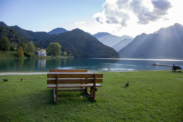 picnic tables and benches in the green on the shore of Ledro Lake