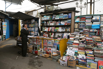 A man browses through books at a second-hand book market in Lima