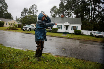 A man points to water coming from Neuse River as it starts flooding houses before Hurricane Florence comes ashore in New Bern