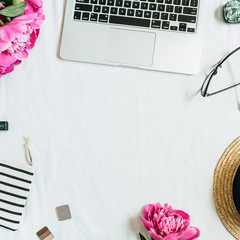 Flat lay, top view frame of women office desk with laptop, pink peony flower bouquet, glasses, straw hat, cosmetics. Fashion or beauty blog background.