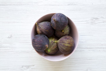 Fresh figs in a pink bowl on a white wooden table. Top view, overhead, from above.