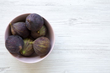 Fresh figs in a pink bowl on a white wooden table. Top view, overhead, from above. Copy space.