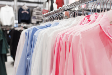 Shirts on hangers in the store, close-up.