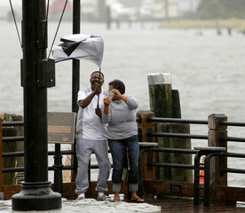 A couple taking pictures on the banks of the Cape Fear River contend with gusts as their umbrella breaks, before the arrival of Hurricane Florence in Wilmington, North Carolina