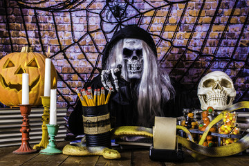 man in black Grimm reaper robe skull mask pointing at camera with skeleton hands surrounded by human skull jack o lantern yellow snake burning candles and Halloween candy