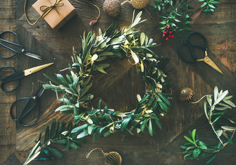 Foto op Aluminium Olijfboom Getting ready for Christmas. Flat-lay of green olive branch festive wreath, Christmas tree decoration toys, gift box and scissors over rustic wood table background, top view, horizontal composition