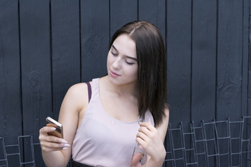 Portrait of young elegant woman outside using phone