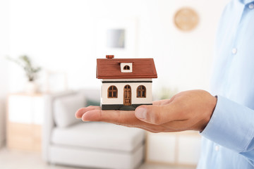 Real estate agent holding house model on blurred background