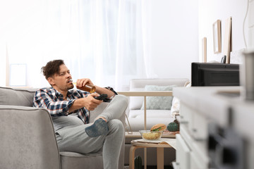 Lazy man with bottle of beer and chips watching TV at home