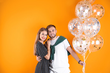 Young couple with air balloons on color background