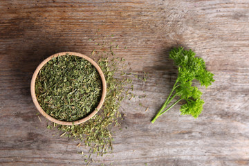 Bowl with dry parsley on wooden background, top view