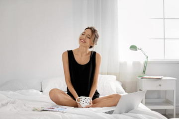 Young happy woman with cup of aromatic coffee sitting on bed at home. Lazy morning