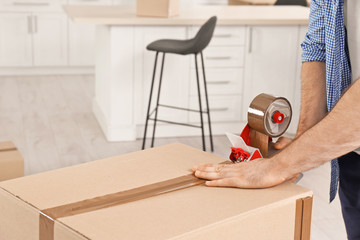 Man packing moving box indoors, closeup. Space for text