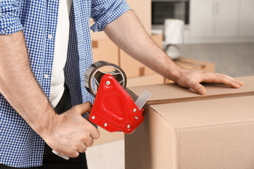 Man packing cardboard box indoors, closeup. Moving day