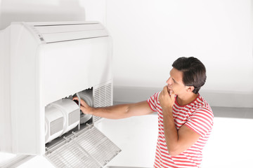 Young man fixing air conditioner at home