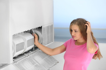 Young woman fixing air conditioner at home