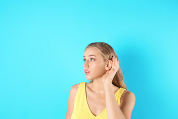 Young woman with hearing problem on color background