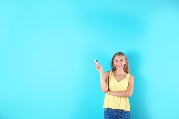 Young woman with air conditioner remote on color background, copy space text