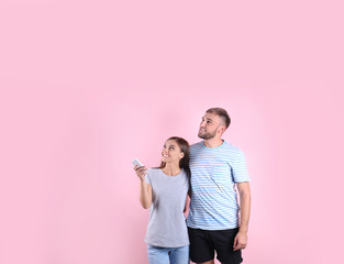Young couple with air conditioner remote on color background