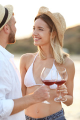 Young couple with glasses of wine on beach