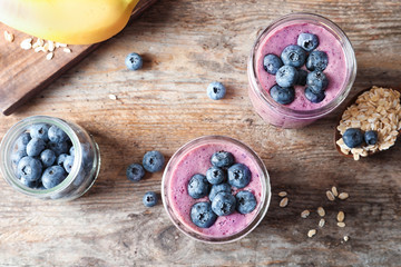 Flat lay composition with blueberry smoothies on wooden background
