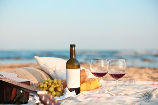 Blanket with food, wine and guitar on beach. Romantic picnic for couple