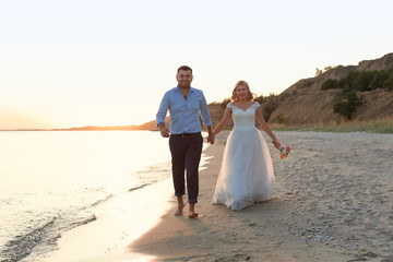 Wedding couple. Bride and groom walking at sunset on beach