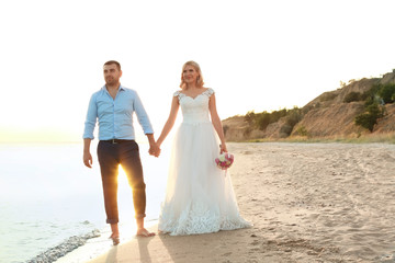 Wedding couple holding hands together on beach. Space for text